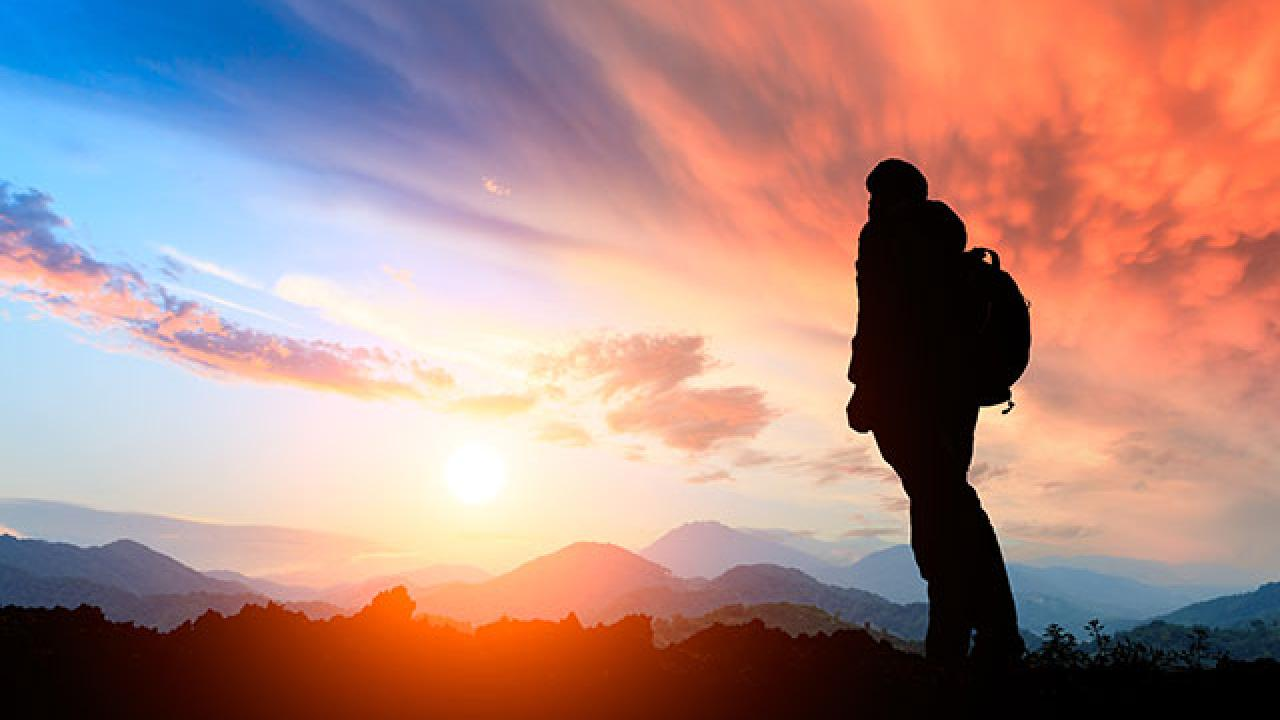 Photo of hiker looking at sunset.