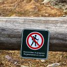 A trail closure sign hanging on a fallen tree.